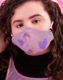 Close up of a face mask with purple appliqued hearts.